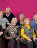 a group of nursing home residents against a pink backdrop
