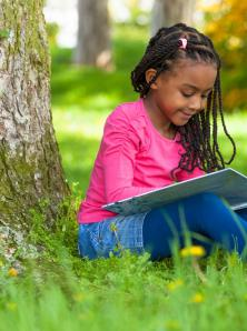 Child reading outdoors